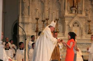 Karen hands the gifts for Holy Communion to Bishop Zubik